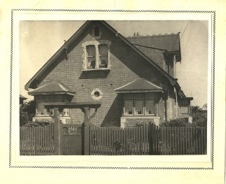 Black and white photograph of the outside of a cottage-style house.